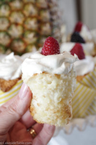 pineapple angel food cake cupcake unwrapped with cool whip and raspberry on top