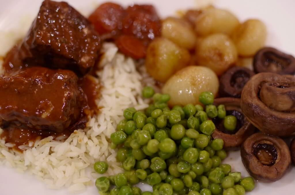 beef bourguignon nested on rice placed with peas, onions and mushrooms