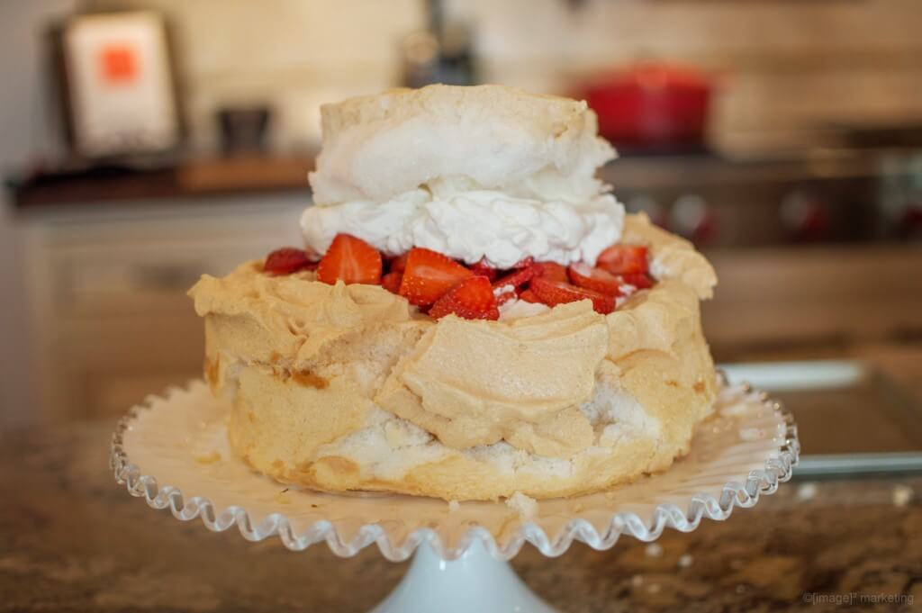 Strawberry Schaum Torte with whip cream and strawberries on a white pedestal cake plate