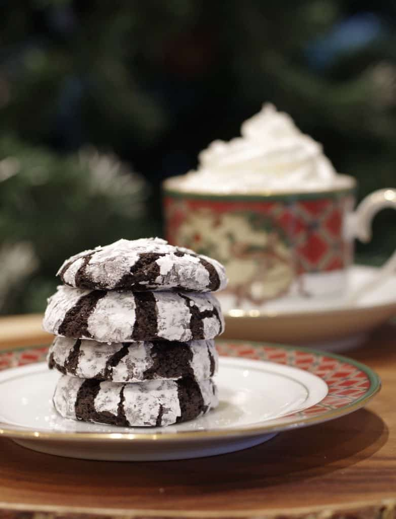 4 cookies stacked in front of a cup of cocoa with whipcream