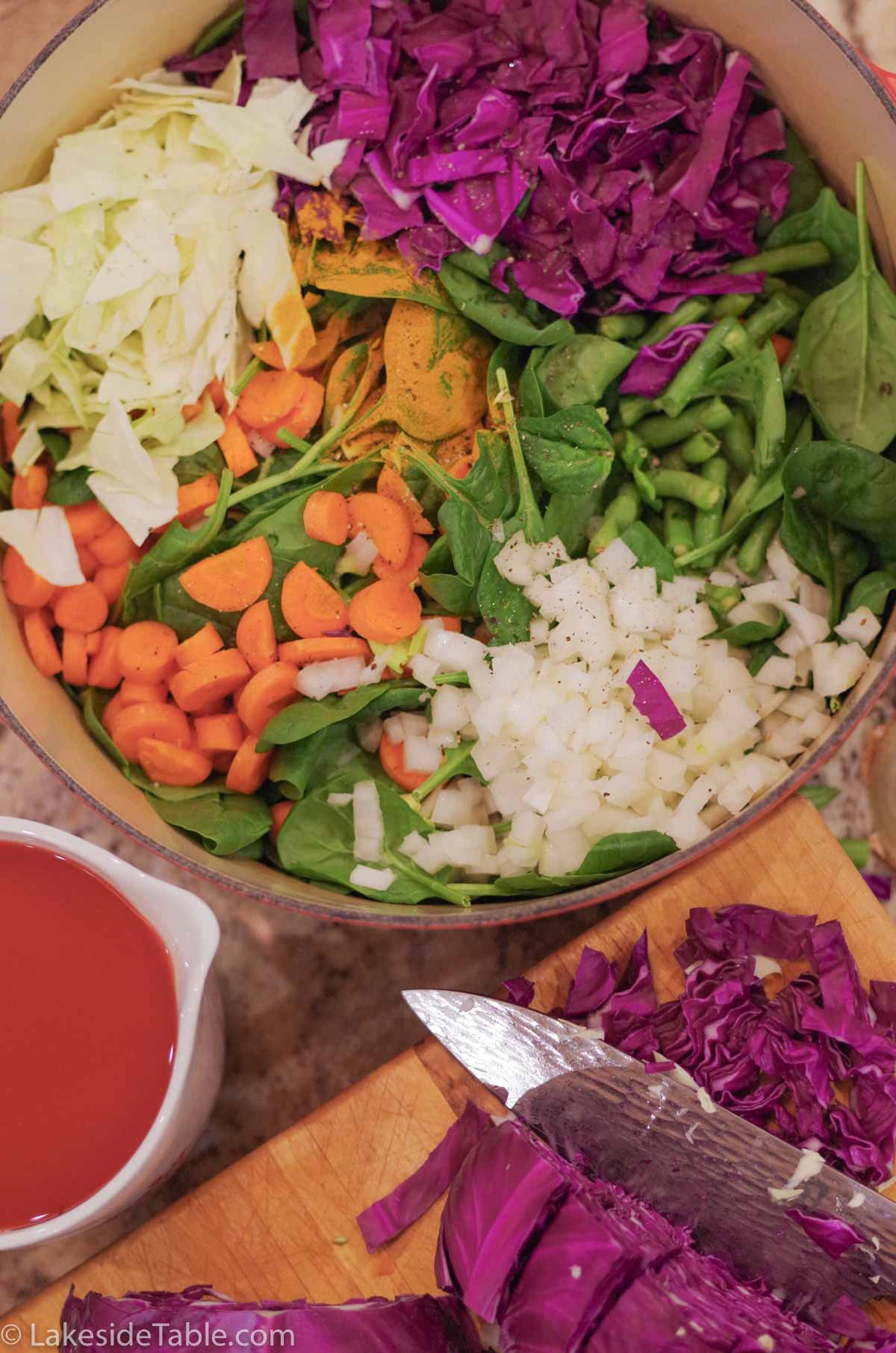soup pot filled with purple cabbage, white onions, orange carrots, green herbs