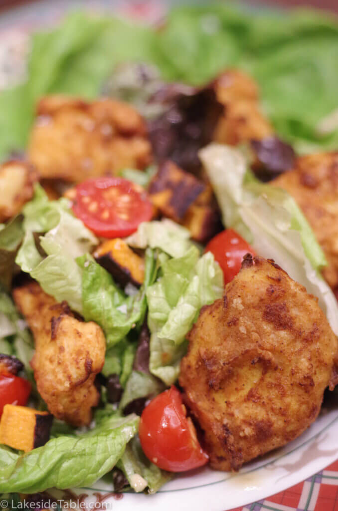 close up view of fried chicken salad with bits of sweet potato, lettuce, fried chicken and tomato