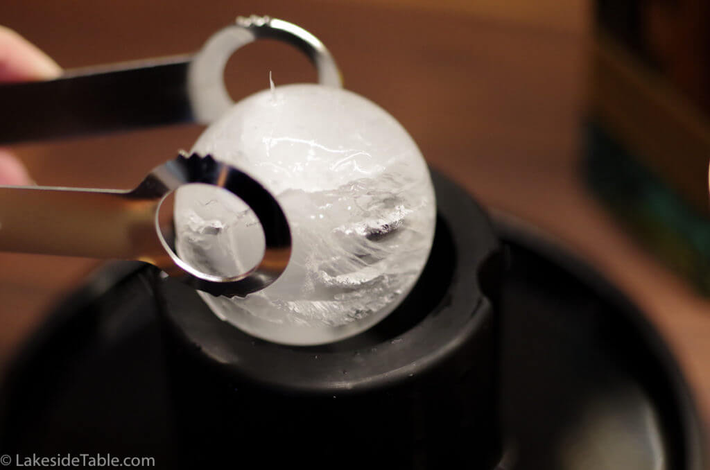 close up of spherical ice ball in tongs