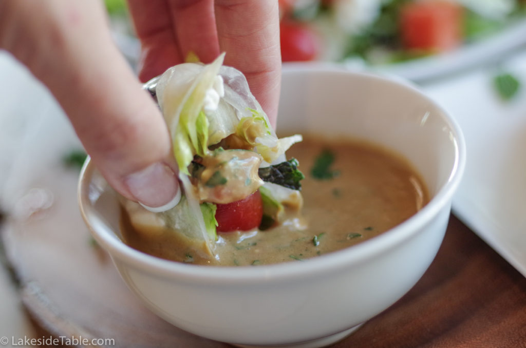 Dipping the salad rollup in the dressing. Yum! | www.lakdesidetable.com