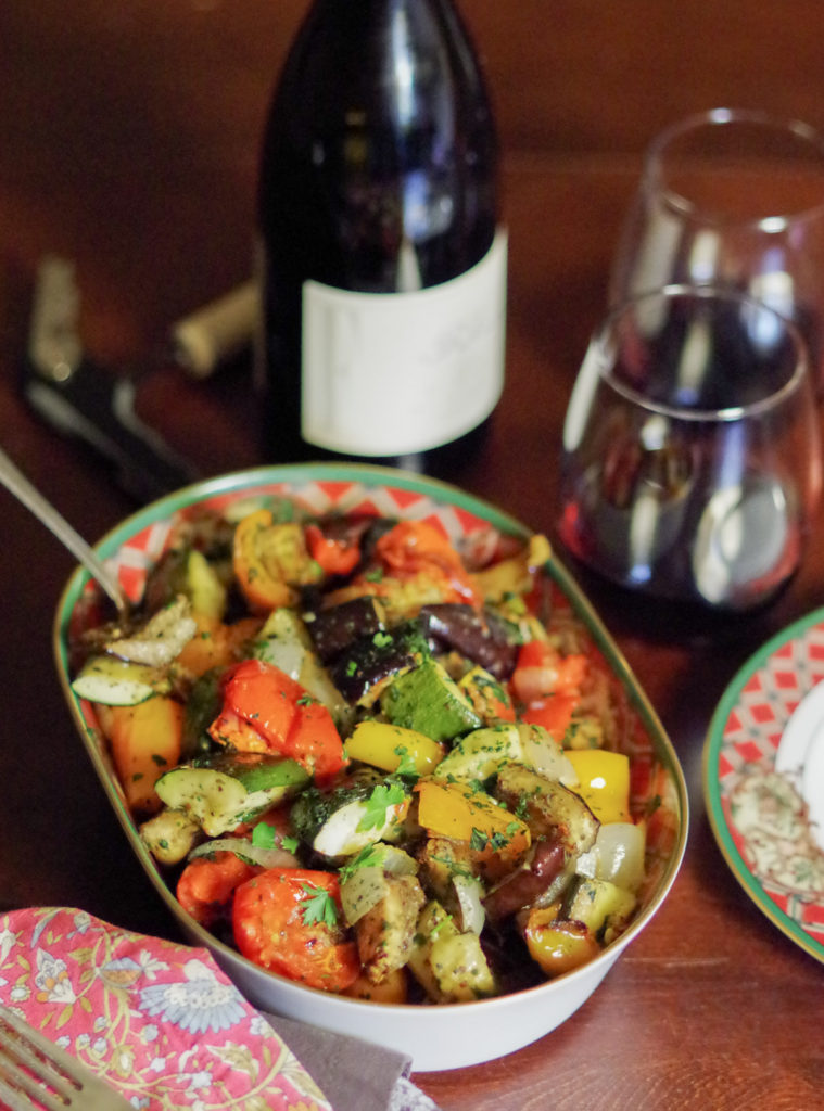 Easy Thanksgiving Side Dishes: bowl of colorful ratatouille with peppers, tomatoes, onion and zucchini. Next to a wine bottle an wine glass