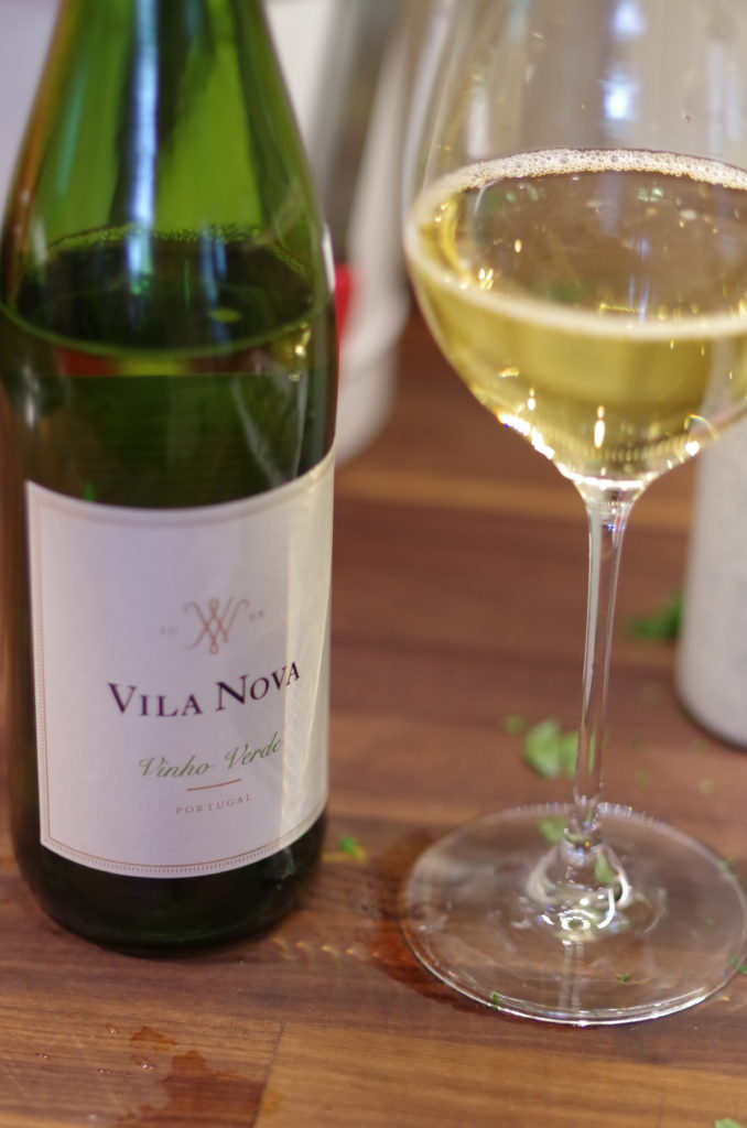 A glass of white wine next to a green bottle of Villa Nova vinho verde