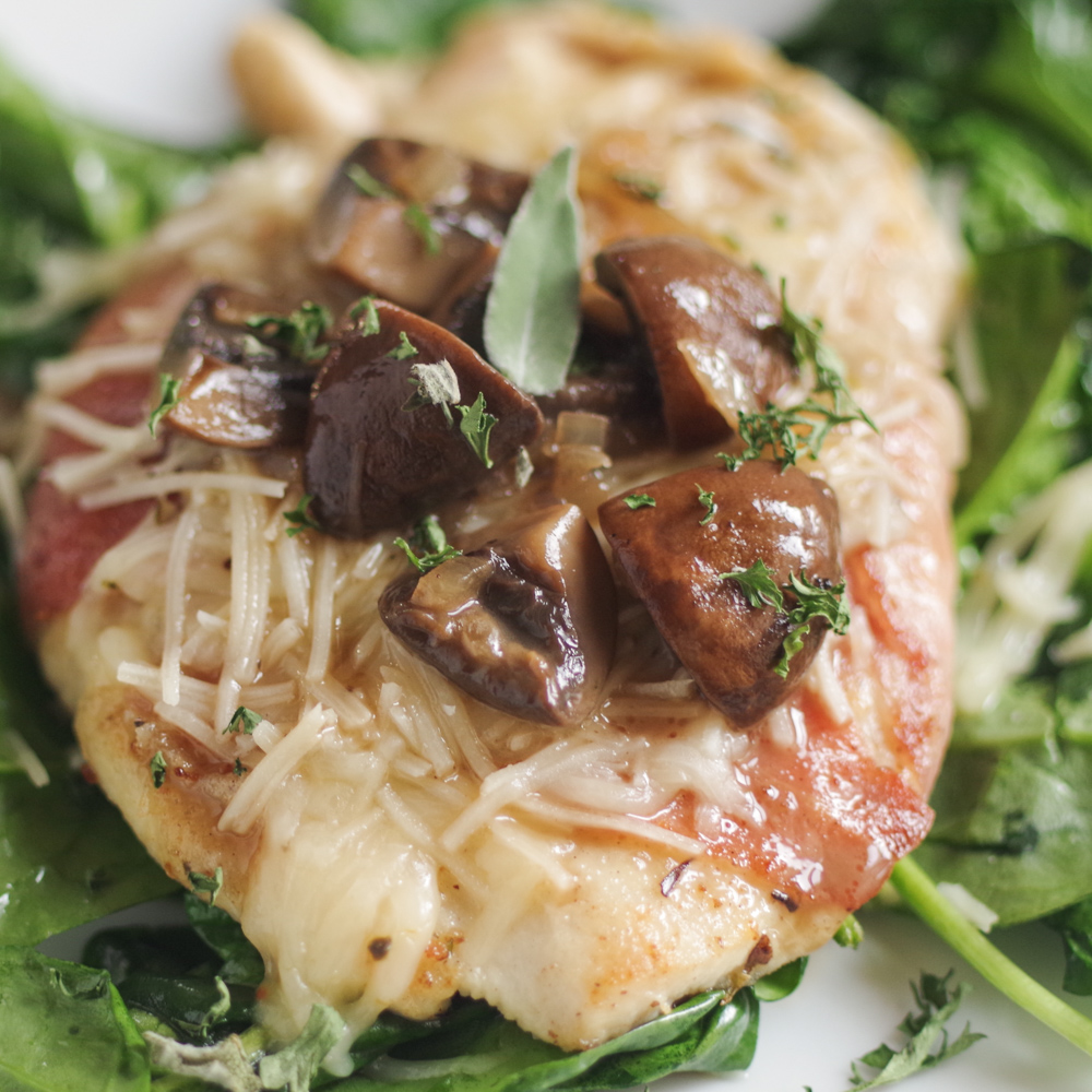 Chicken wrapped in prosciutto covered in mushrooms and cheese over spinach