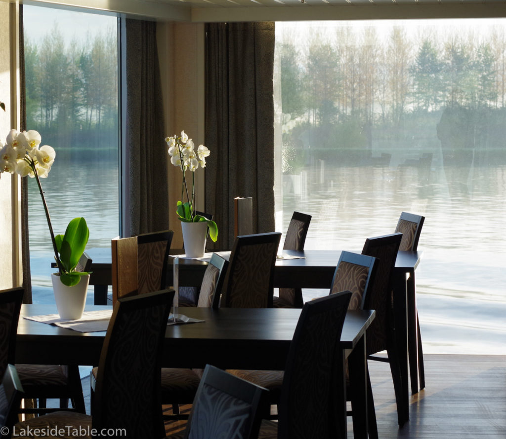 tables and chairs surrounded by windows over looking a river