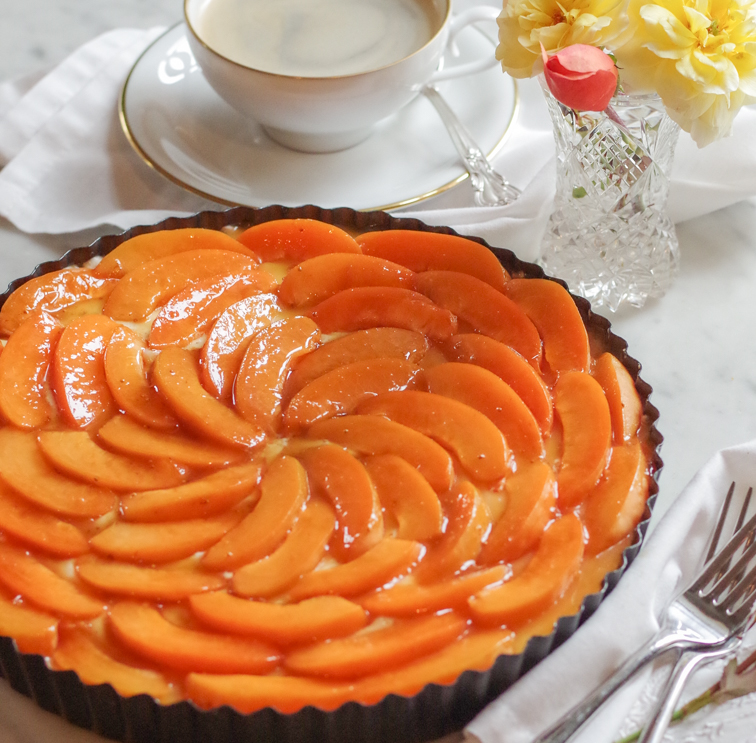 apricot tart next to a cup of coffee and peach and yellow roses in a crystal vase