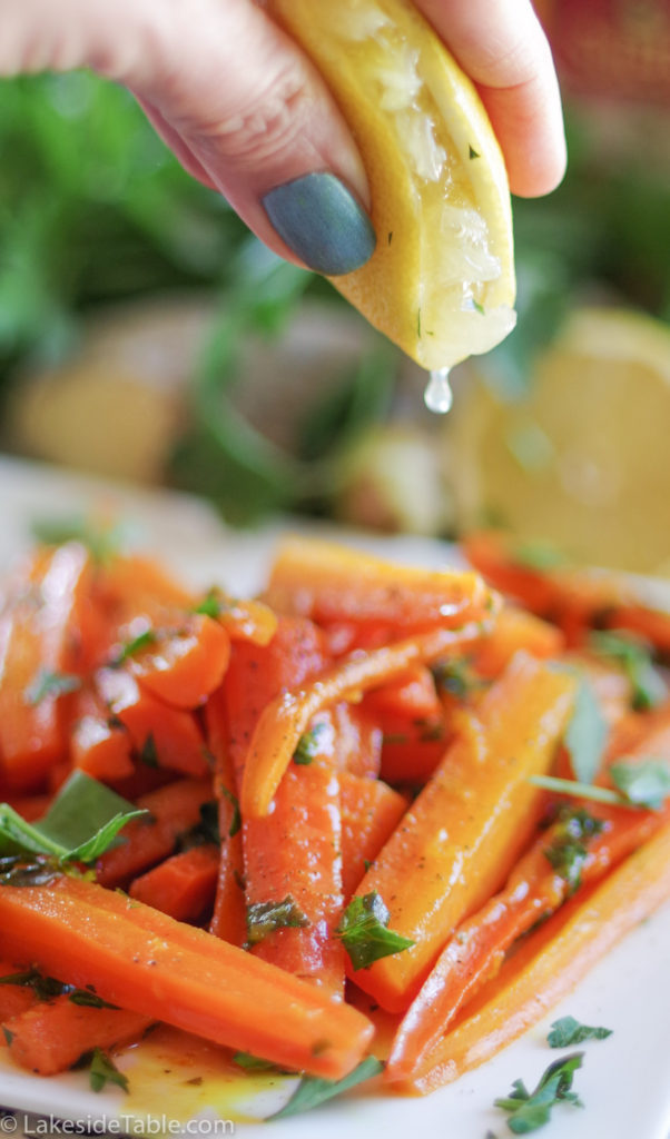 Easy Thanksgiving side dishes: turmeric honey glazed carrot recipe - plate of carrots cut into long match sticks, sprinkled with parsley. Behind this is an array of fresh parsley and lemons.