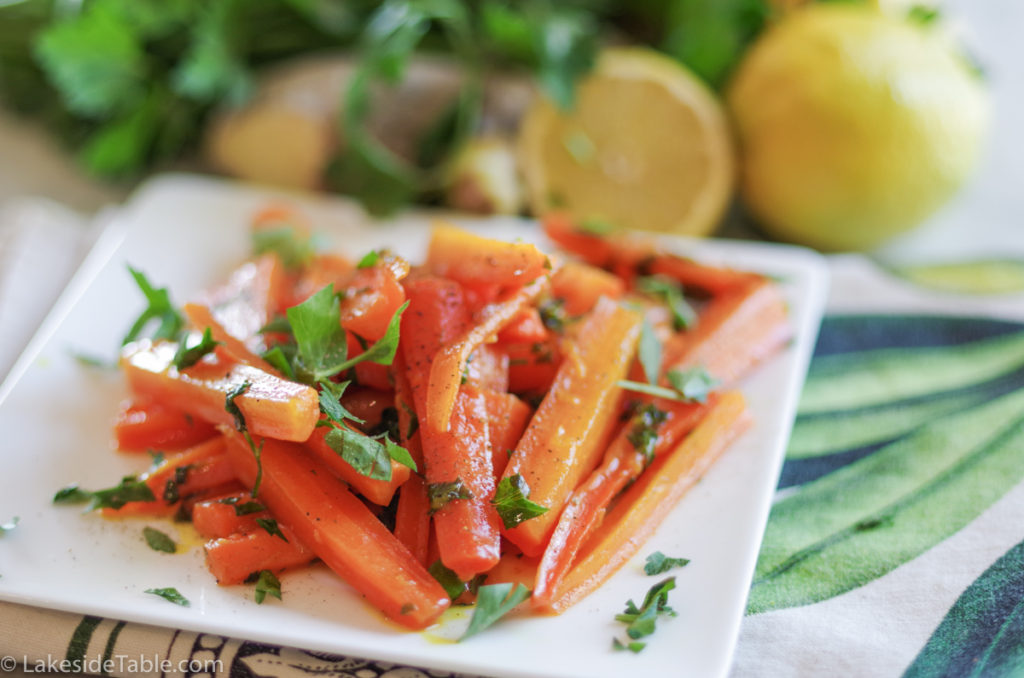 turmeric honey glazed carrot recipe - plate of carrots cut into long match sticks, sprinkled with parsley. Behind this is an array of fresh parsley and lemons.