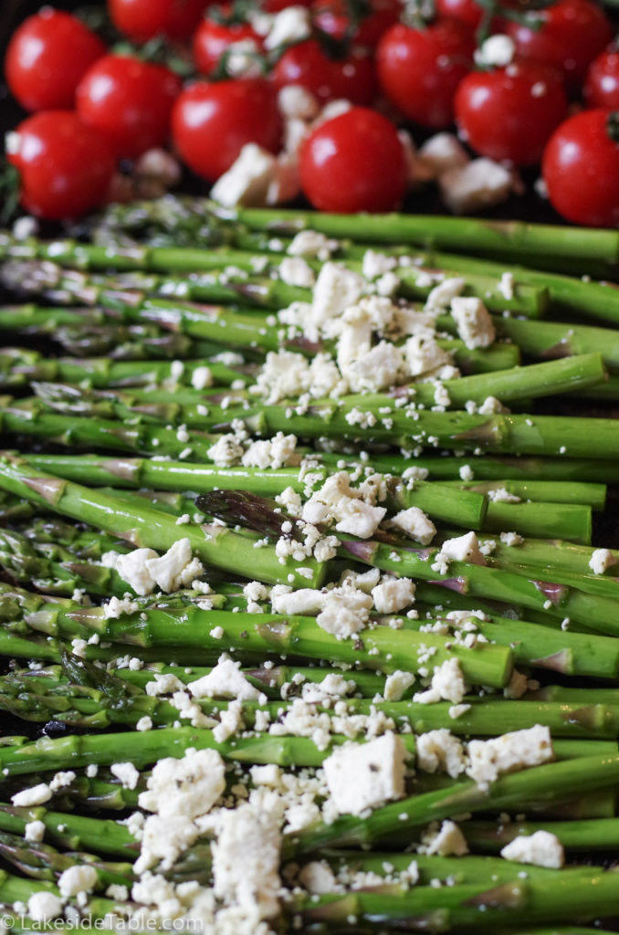Bright green asparagus laid out on a baking sheet with white feta sprinkled on top in front of bright red cherry tomatoes