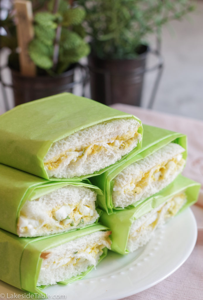 egg salad sandwiches on a plate made with white bread and wrapped in green paper