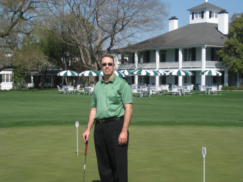 Man in a green shirt and black pants standing in front of the club house on the Augusta golf course