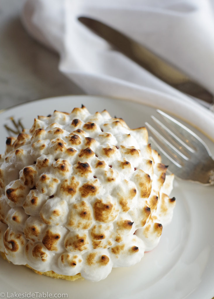 An ice cream ball covered in toasted meringue on a white plate with a fork