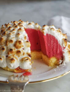 close up of an ice cream bombe dessert with raspberry red ice cream, yellow pound cake and toasted meringue on top