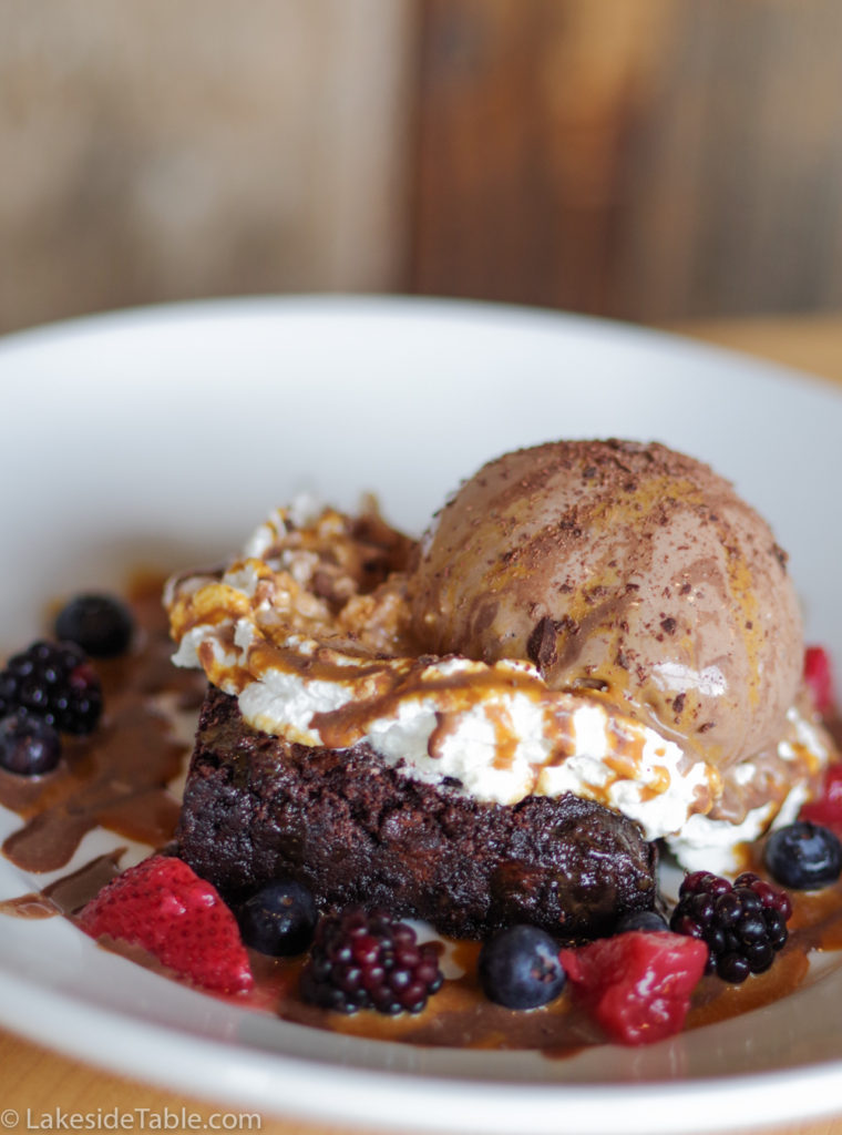 ice cream flavors brownie sundae with chocolate ice cream, whip cream, berries and caramel sauce