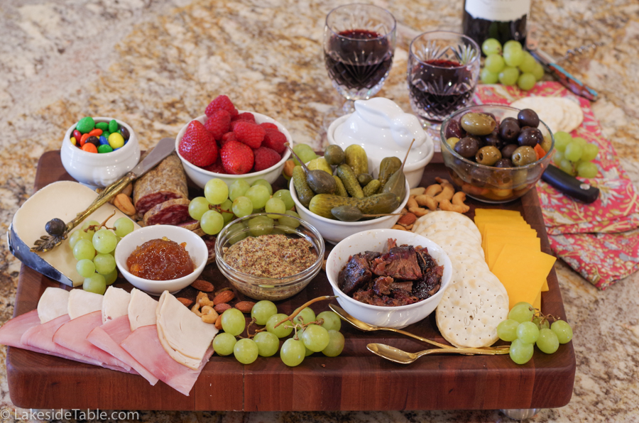 A cutting board loaded down with tons of meats, cheese, fruit and nuts
