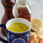 Hot mug of a yellow turmeric tonic with ice next to fresh turmeric root, ginger, lemon, honey and pepper