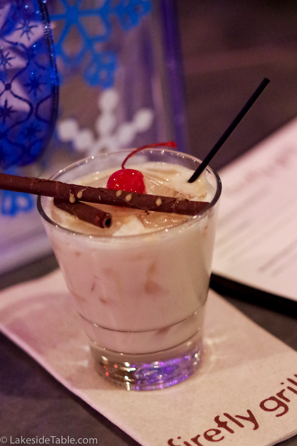 white creamy cocktail on ice with a cherry and chocolate cigars