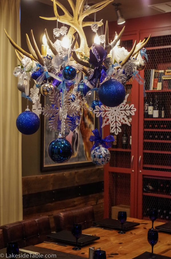 Antler chandelier with blue and silver balls and snowflakes over a dining table