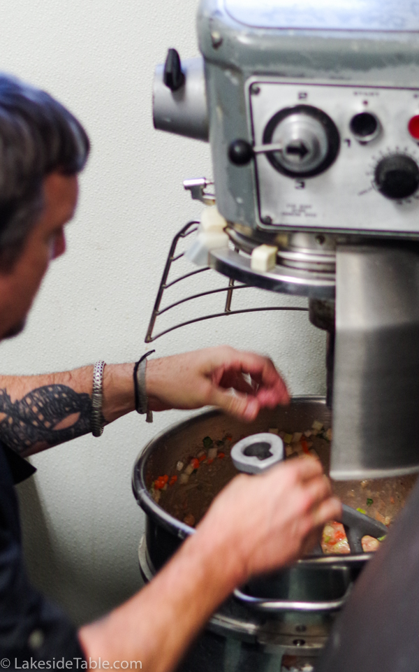 chef pulling out a giant bowl of an enormous mix master