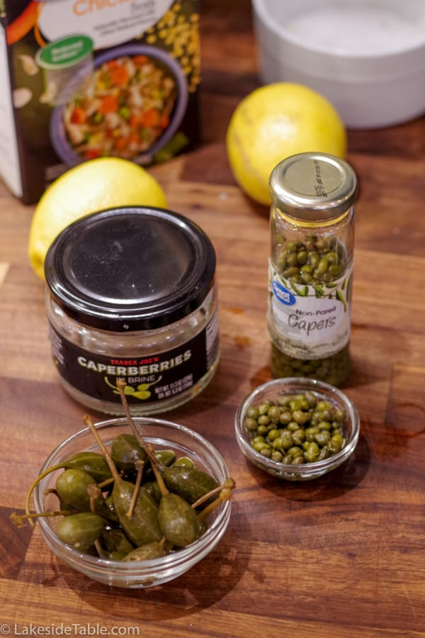 Jars of caperberries and capers with small bowls of each