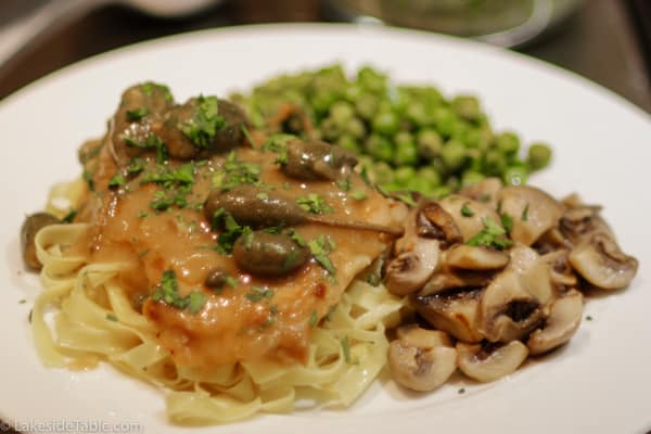 turkey piccata with a side of peas and mushrooms