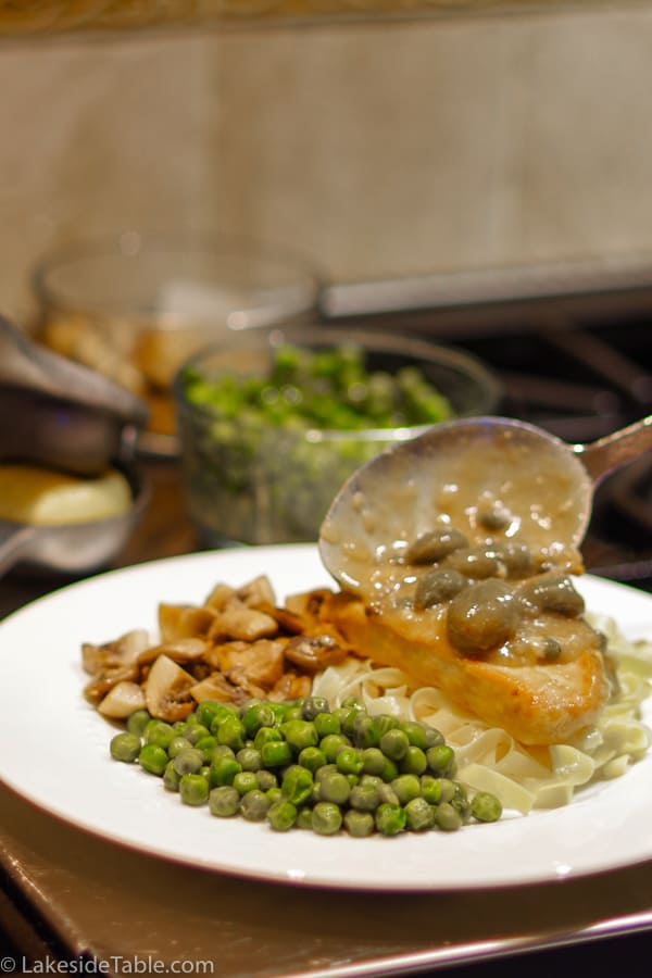 spooning piccata sauce over turkey with a side of peas and mushrooms