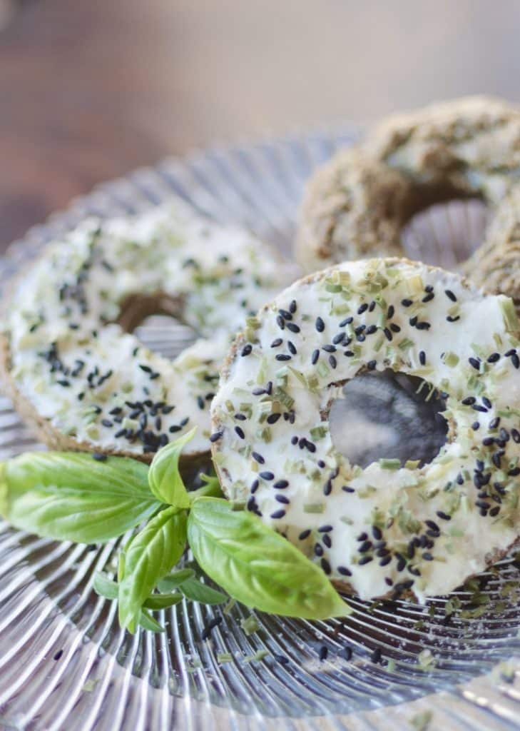 3 low carb bagel with cream cheese, chives and black sesame seeds on a glass plate with a sprig of basil