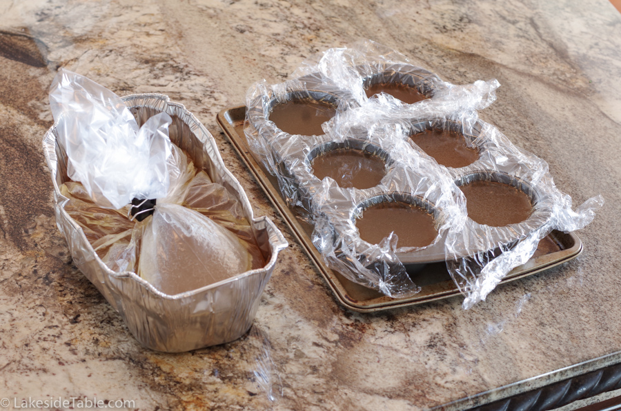 liquid broth in muffin tin lined with plastic wrap sitting on a baking sheet and a large bag of broth closed with a binder clip sitting in a foil tin bread pan