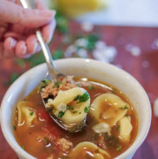 Easy tortellini soup with turkey sausage and parmesan cheese in a white bowl with a spoonful ready to eat