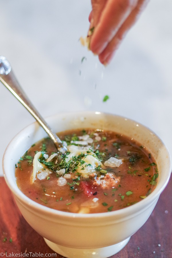 sprinkling parmesan on easy tortellini soup