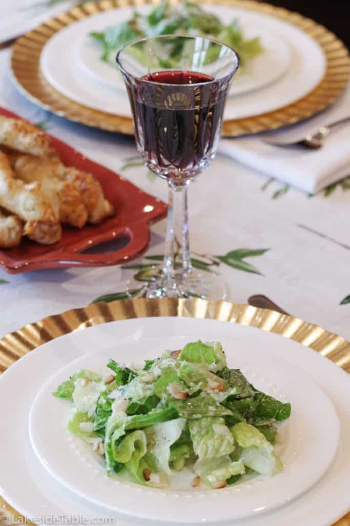 Simple salad with parmesan dressing on a white plate with a gold charger with a crystal glass of red wine