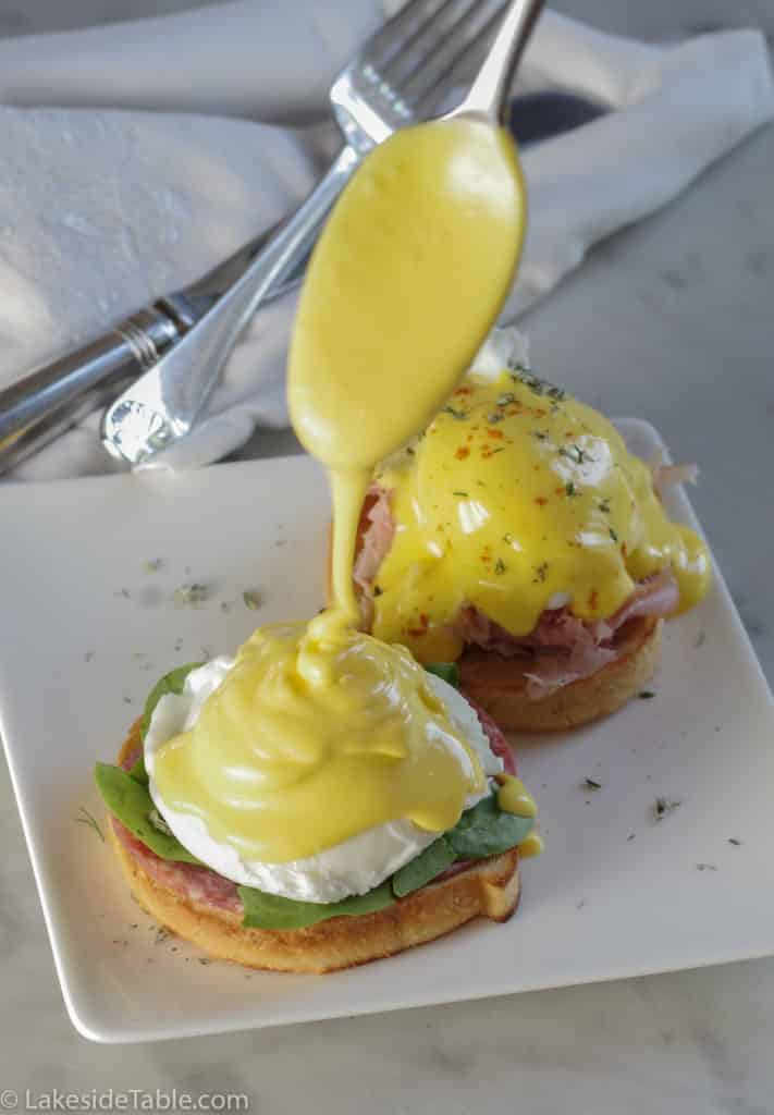 pouring golden yellow classic hollandaise sauce over poached egg and english muffin