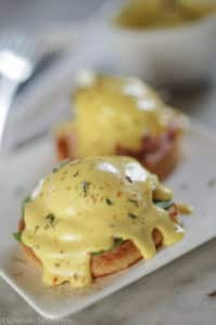 golden yellow classic hollandaise sauce over poached egg and english muffin