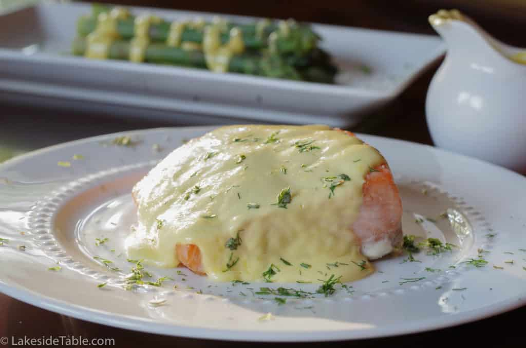 classic hollandaise sauce over baked salmon on a white plate with asparagus in the background