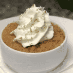 key lime pie with crust on top with whip cream and green lime zest