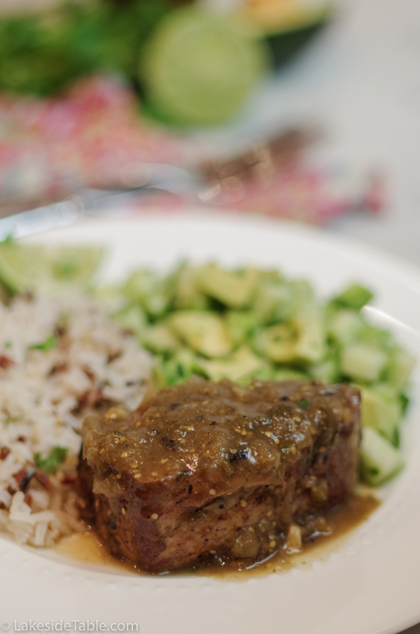 plate of pork with chili verde, cucumber salad and rice