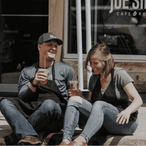 Emily and Brennan sitting outside their cafe laughing