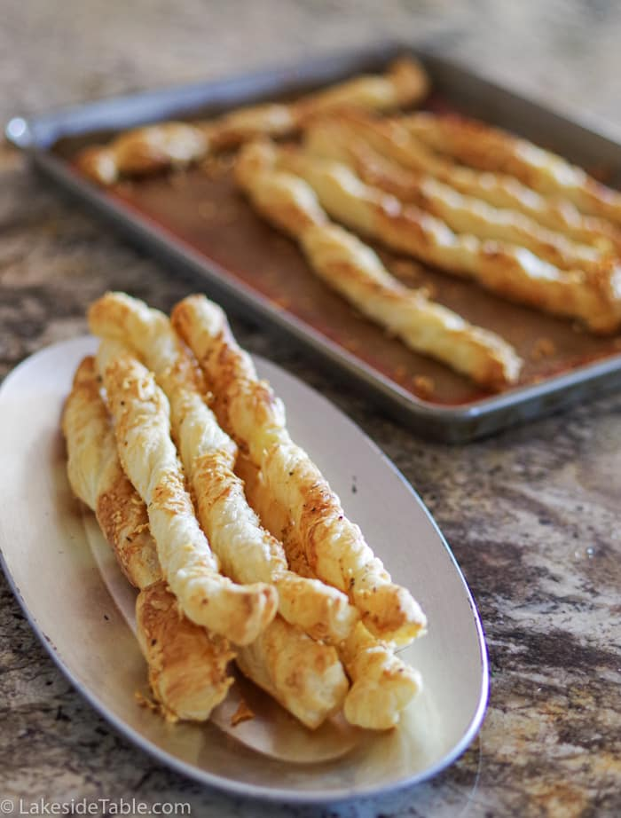 Golden brown garlic parmesan breadsticks piled on a white plate with a baking sheet of more behind