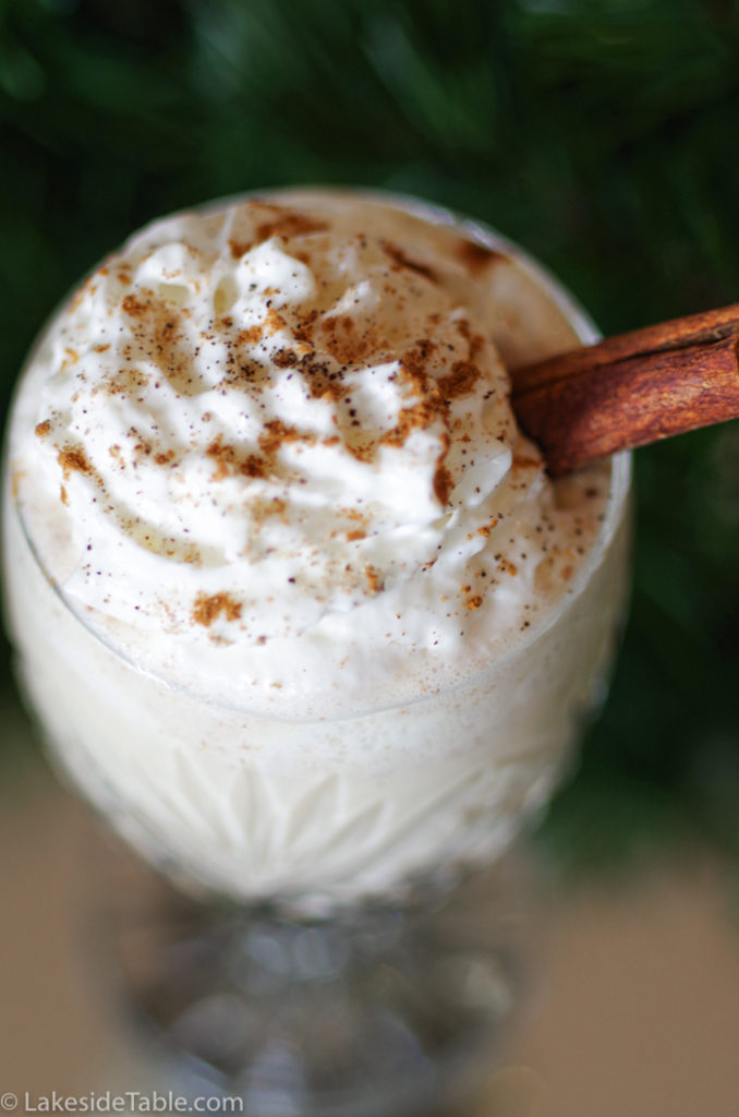 close up of a glass of homemade egg nog with whip cream and a cinnamon stick topped with ground nutmeg