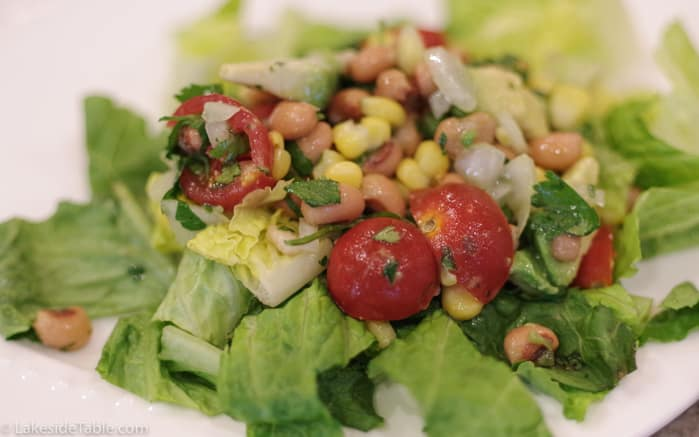 Cowboy caviar over lettuce on a white plate