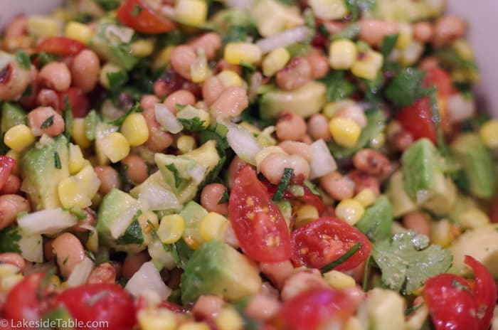 Close up of Cowboy Caviar with avocado, corn, black eye peas, tomatoes and lime