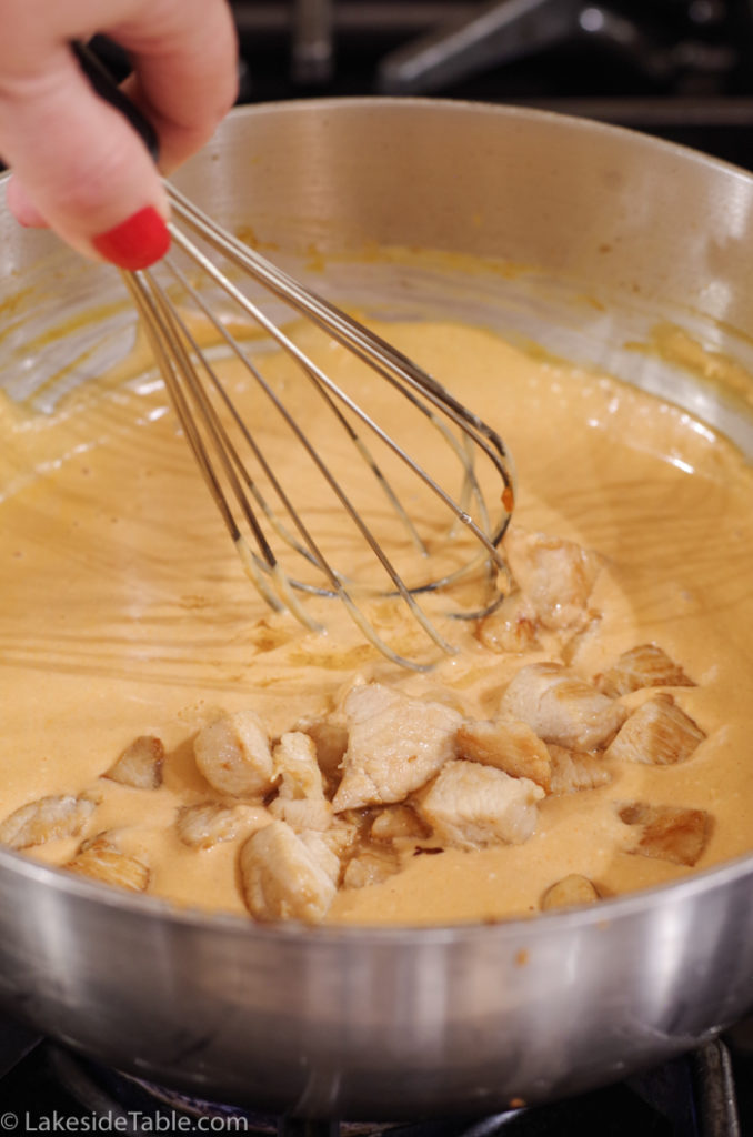 stirring chicken into dip