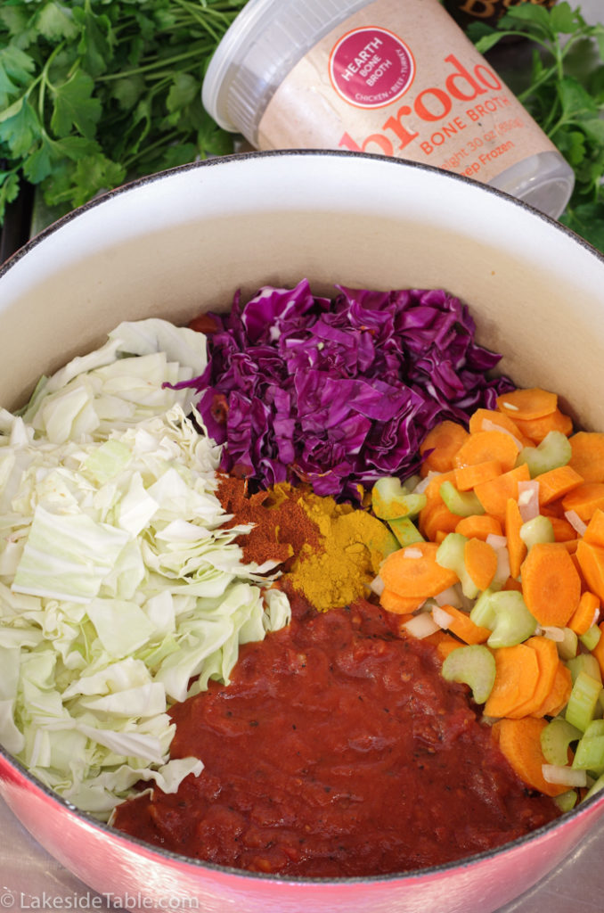 top down view into soup pot, no broth added yet, purple cabbage, green cabbage, red tomatoes and orange carrots mixed with green celery