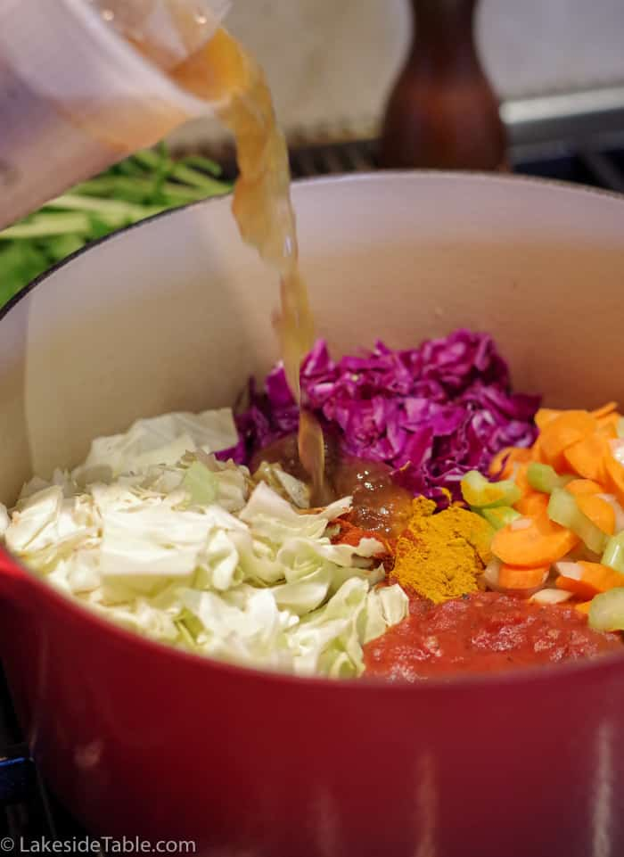 Pouring broth into detox cabbage soup