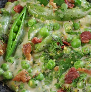 close up of creamy peas with bits of bacon in a black bowl