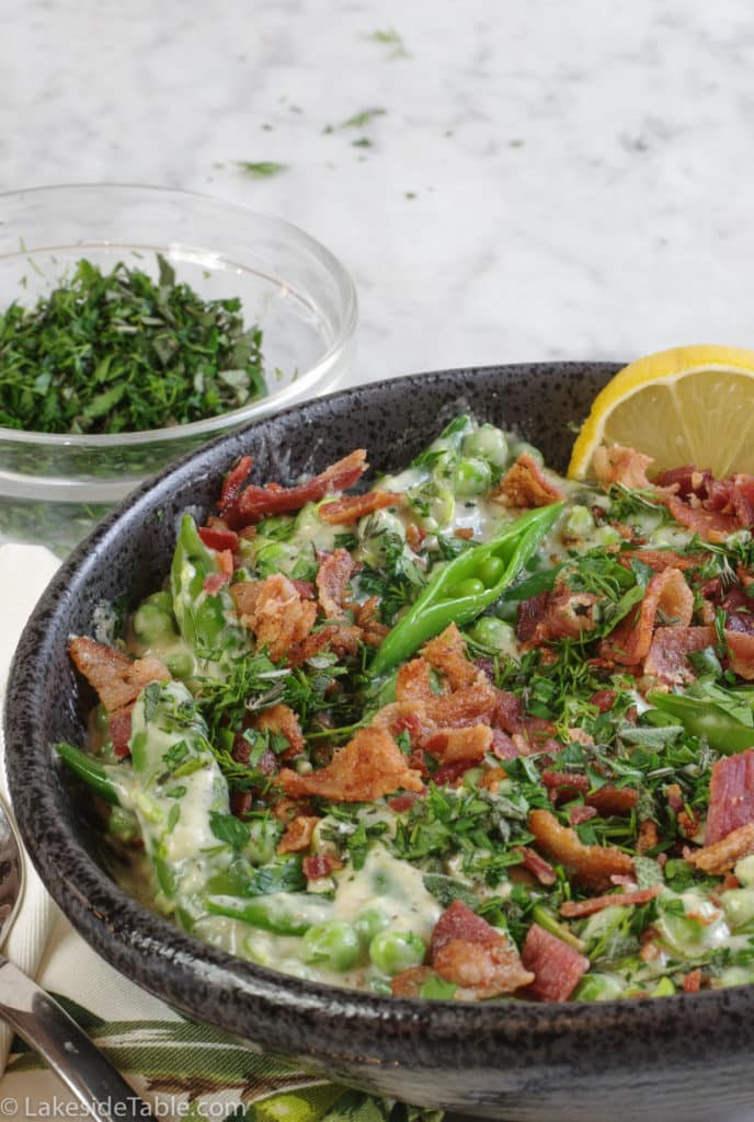 A big black bowl filled to the brim with garden peas and sugar snap peas still in their pods topped with crispy bacon and chopped fresh herbs, garnished with a yellow lemon wedge
