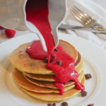 raspberry sauce being poured over chocolate chip pancakes